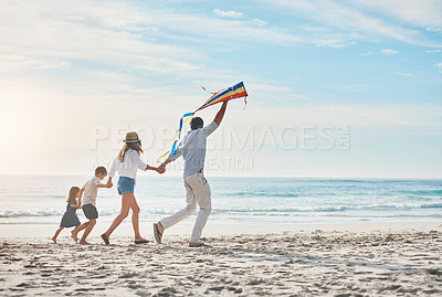 Buy stock photo Full length shot of a happy couple holding hands with their children and walking along the beach with a kite