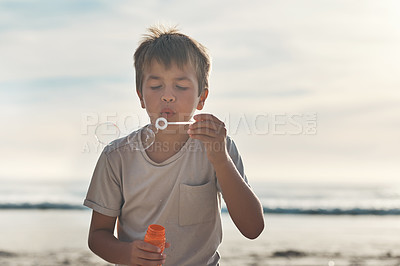 Buy stock photo Cropped shot of a young boy standing alone and blowing bubbles during a day on the beach