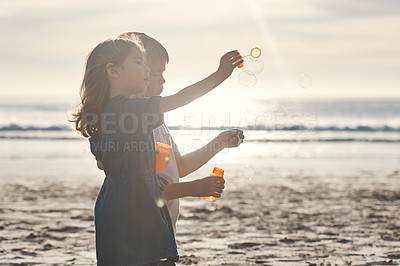 Buy stock photo Cropped shot of two young siblings standing together and blowing bubbles during a relaxing day on the beach