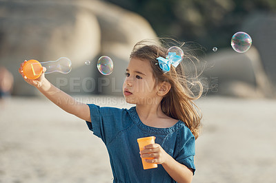 Buy stock photo Cropped shot of a young girl standing alone and blowing bubbles during an enjoyable day on the beach