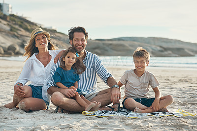 Buy stock photo Full length portrait of an affectionate couple sitting with their two children and enjoying a day on the beach together