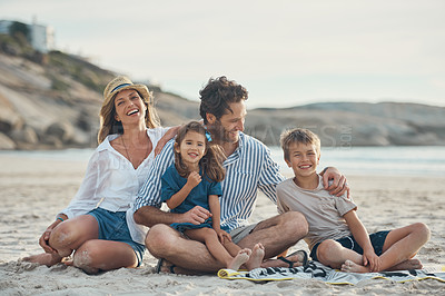 Buy stock photo Full length shot of an affectionate couple sitting with their two children and enjoying a day on the beach together