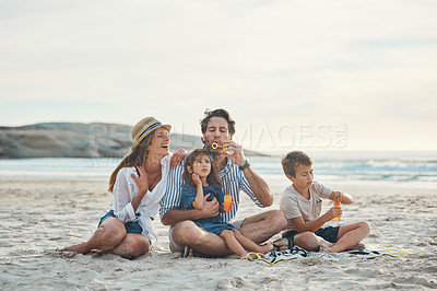 Buy stock photo Full length shot of a happy couple sitting with their two children who are blowing bubbles on the beach