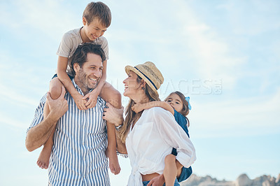 Buy stock photo Cropped shot of a happy young couple carrying their two children during an enjoyable day on the beach