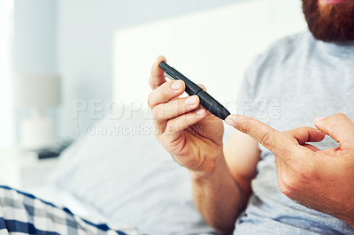 Buy stock photo Cropped shot of an unrecognizable man checking his blood sugar levels