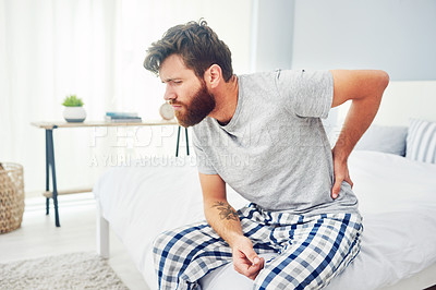 Buy stock photo Cropped shot of a young man experiencing back pain at home