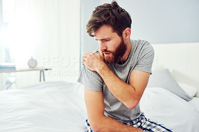 Buy stock photo Cropped shot of a young man experiencing shoulder pain while sitting on his bed