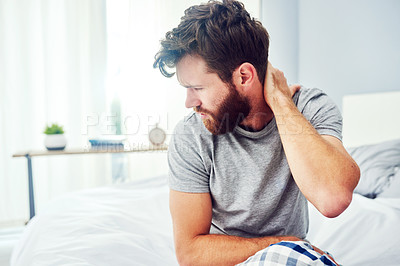 Buy stock photo Cropped shot of a young man experiencing neck pain
