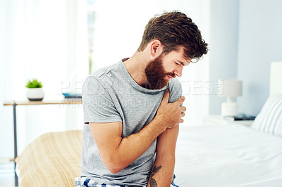 Buy stock photo Cropped shot of a young man experiencing discomfort in his upper arm