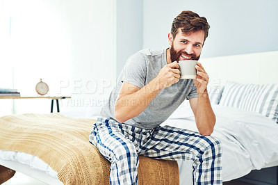 Buy stock photo Shot of a young man having a cup of coffee while sitting in his bedroom