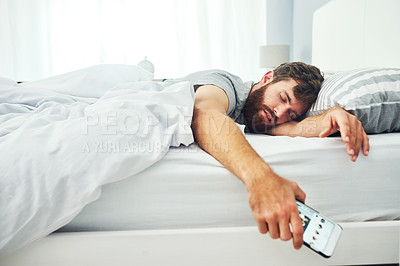 Buy stock photo Shot of a young man sleeping with his cellphone in his hand