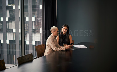Buy stock photo Shot of two attractive young businesswomen using a cellphone while having a meeting together in an office