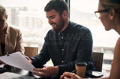 Buy stock photo Shot of a group of young businesspeople going through paperwork and discussing ideas during a meeting at work