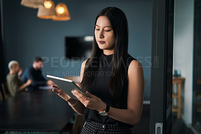 Buy stock photo Shot of an attractive young businesswoman using a digital tablet in an office with her colleagues in the background