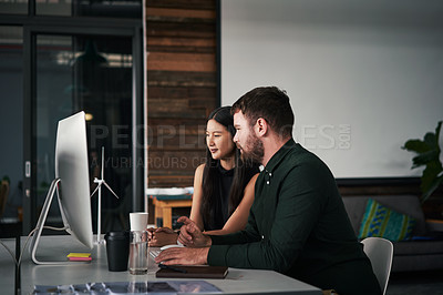 Buy stock photo Shot of two young businesspeople working on a computer together inside an office