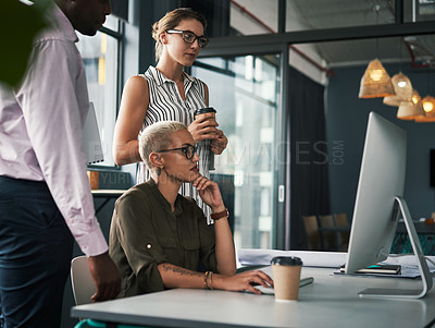Buy stock photo Shot of a group of young businesspeople working on a computer together inside an office