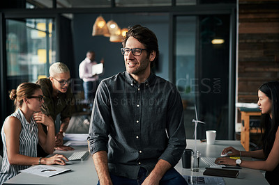 Buy stock photo Shot of a handsome businessman standing inside an office with his colleagues working in the background