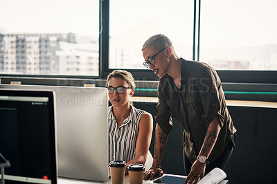 Buy stock photo Shot of two attractive young businesswoman working together on a computer inside an office