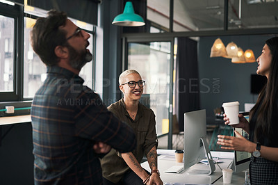 Buy stock photo Shot of a group of businesspeople having a conversation together at work