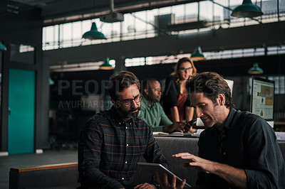 Buy stock photo Shot of two mature businessmen using a digital tablet together at work with their colleagues in the background