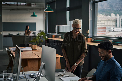 Buy stock photo Shot of two young businesspeople working together in a modern office