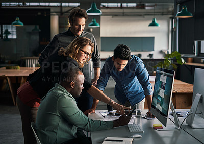 Buy stock photo Shot of a group of businesspeople using a cellphone together inside a modern office