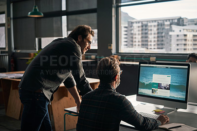 Buy stock photo Shot of two mature businessmen working together on a computer at work