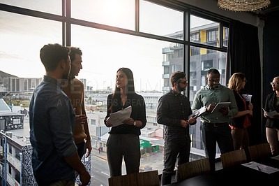 Buy stock photo Shot of a group of businesspeople working and conversing together inside a modern office