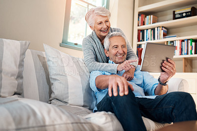 Buy stock photo Shot of a senior couple taking selfie together on the sofa at home