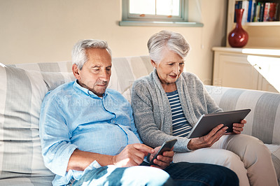 Buy stock photo Shot of a senior couple using their smart devices on the sofa at home