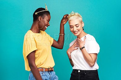 Buy stock photo Studio shot of a young woman putting a crown on her friend against a turquoise background