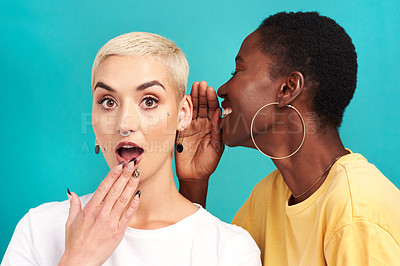Buy stock photo Studio shot of a young woman whispering in her friend's ear against a turquoise background