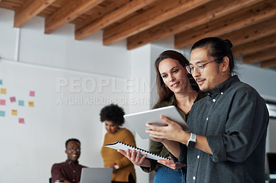 Buy stock photo Shot of two young businesspeople using a digital tablet together at work with their colleagues in the background