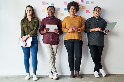 Buy stock photo Full length shot of a group of a young businesspeople standing together and using their digital devices at work