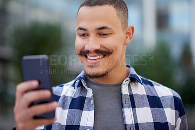 Buy stock photo Shot of a confident young man using a smartphone at university