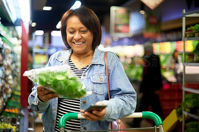 Buy stock photo Shot of a mature woman out shopping for fresh produce in a grocery store