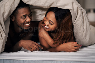 Buy stock photo Cropped shot of an affectionate young couple lying under the covers on their bed at home