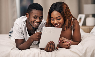 Buy stock photo Cropped shot of an affectionate young couple using a tablet while lying on their bed at home
