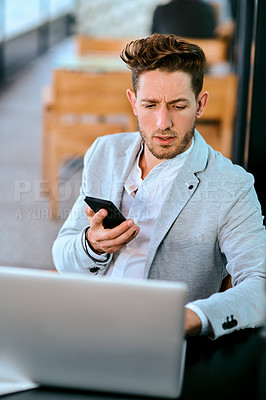 Buy stock photo Shot of a young businessman using a laptop and smartphone in a cafe
