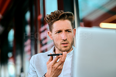 Buy stock photo Shot of a young businessman using a laptop and smartphone in at a sidewalk cafe