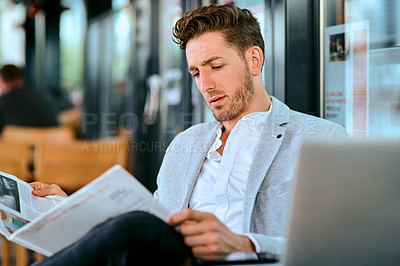 Buy stock photo Shot of a young businessman reading a newspaper at a sidewalk cafe