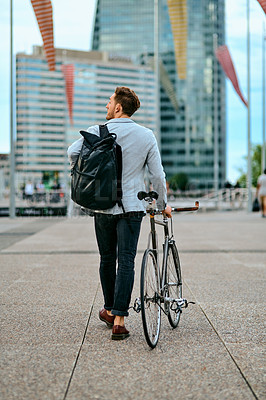 Buy stock photo Rearview shot of a young businessman traveling through the city with his bicycle