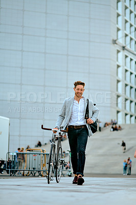 Buy stock photo Shot of a young businessman traveling through the city with his bicycle