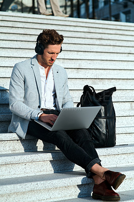 Buy stock photo Shot of a young businessman using a laptop on the steps in a city