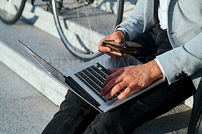 Buy stock photo Cropped shot of a businessman using a laptop and credit card on the steps in a city