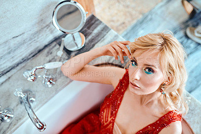 Buy stock photo Shot of a glamorous young woman dressed in elegant wear sitting in a bathtub