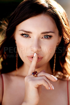 Buy stock photo Shot of a beautiful young woman putting her finger on her lips outdoors