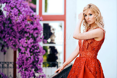 Buy stock photo Shot of a beautiful young woman dressed in elegant wear standing on a balcony