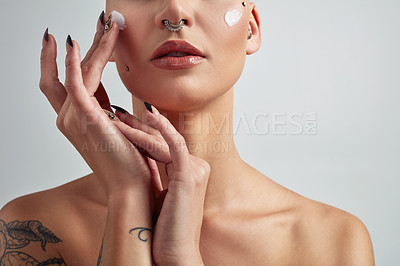 Buy stock photo Shot of an unrecognizable woman applying moisturizer on her face against a grey background