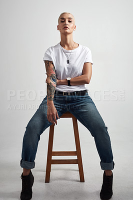 Buy stock photo Full length shot of a stylish young woman sitting on a stool against a grey background